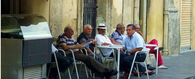 anziani parlano al bar seduti sui tavolini fuori