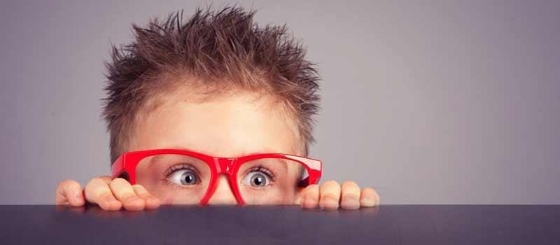 bimbo-occhiali-rossi-sporge-da-tavolo-guarda-di-soppiatto