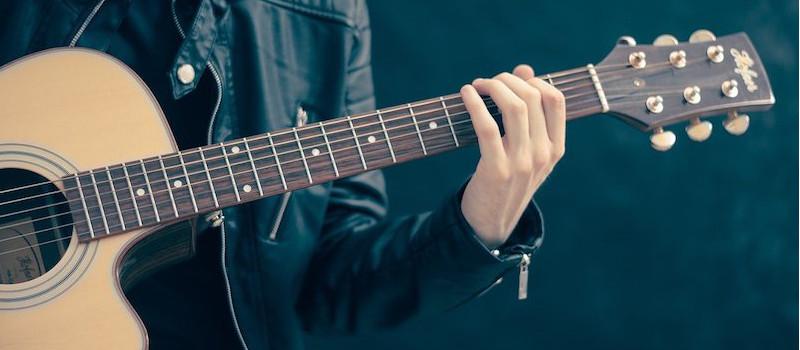 chitarra-in-primo-piano-suonata-da-ragazzo-con-giacca-di-pelle