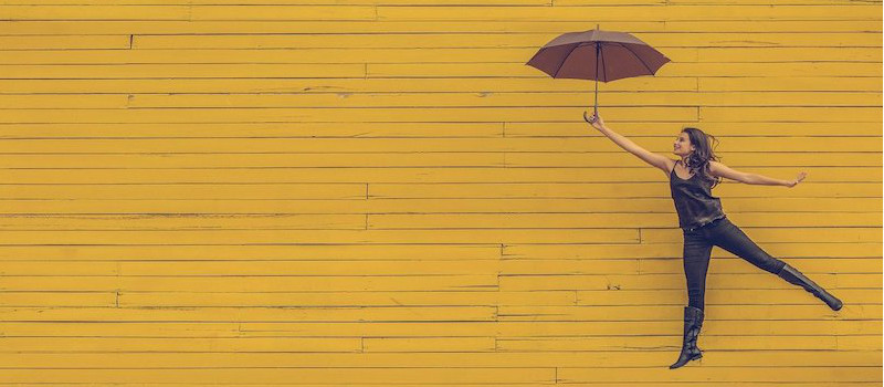 ragazza con ombrello sfondo giallo