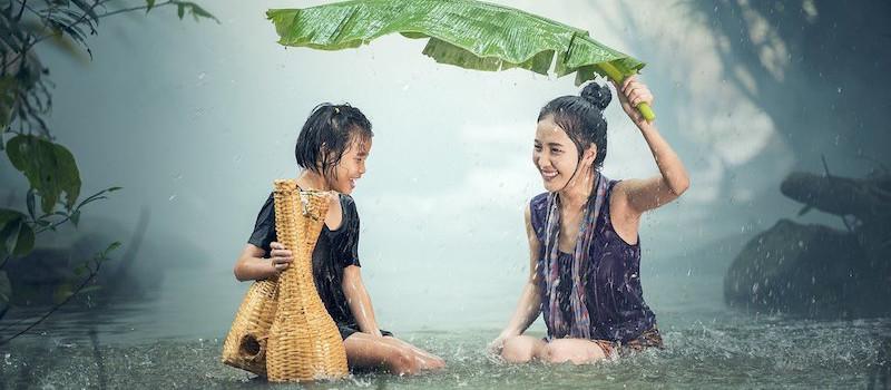 due ragazze giovani fanno il bagno sotto la pioggia
