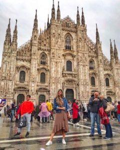 ragazza colombiana con vestito marrone e giacca blu davanti a duomo di Milano